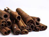 pic of cinnamon sticks  - Stack of cinnamon sticks against a white background - JPG