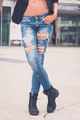 picture of skinny girl  - Detail of a young girl in ripped jeans posing in the city streets - JPG