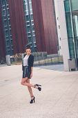 image of mini-skirt  - Gorgeous young brunette in black skirt posing in an urban context - JPG