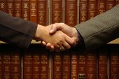 foto of law-books  - a handshake between two people with law books - JPG