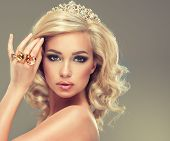 picture of tiara  - Beautiful cute girl  model  with blonde curly hair with  the tiara on her head and large rings on her  hand - JPG