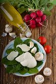 foto of radish  - Vertical photo of traditional twisted slovak cheese on cutting board plus various vegetable around as onions garlics mushrooms and radishes with baby spinach with bottle with homemade lemonade - JPG