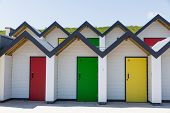 image of beach-house  - Colourful doors of yellow red and green with each one being numbered individually of white beach houses on a sunny day in Swanage - JPG