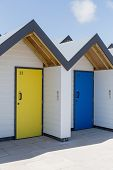 pic of beach-house  - Colourful doors of yellow and blue with each one being numbered individually of white beach houses on a sunny day in Swanage - JPG