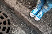 picture of snickers  - Teenager feet in jeans and blue shoes stand on the street edge - JPG