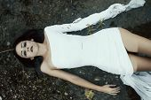 stock photo of mystery  - Woman lying on the shore in white dress - JPG