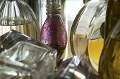 stock photo of perfume  - closeup of a series of small bottles of perfume in backlight - JPG