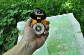 foto of cartographer  - Forest may walk in the woods. Compass in hand against the background of the map. ** Note: Visible grain at 100%, best at smaller sizes - JPG