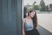 stock photo of curvy  - Beautiful young curvy girl in tank top posing in an urban context - JPG