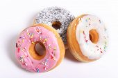 image of donut  - three delicious and tempting donuts with different flavor donuts and toppings isolated on white background in unhealthy nutrition and sugar and sweet cake addiction concept - JPG