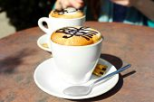 pic of treble clef  - Cups of cappuccino with treble clef on foam on table in cafe - JPG