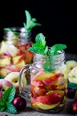 pic of infusion  - Jar delicious refreshing drink of peach fruits and plum with mint on wooden infused water  - JPG