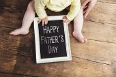 picture of sign board  - Little baby with Happy fathers day sign on wooden background - JPG