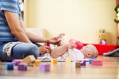stock photo of young baby  - Young hipster father changing nappy to his little baby daughter - JPG