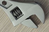 picture of extreme close-up  - adjustable wrench closeup on wooden background - JPG