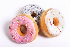 stock photo of flavor  - three delicious and tempting donuts with different flavor donuts and toppings isolated on white background in unhealthy nutrition and sugar and sweet cake addiction concept - JPG