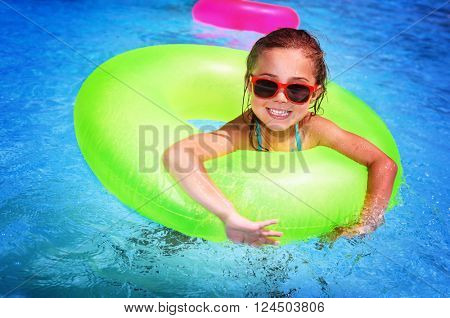 Portrait of cute happy little girl having fun in swimming pool, floating in blue refreshing water wi