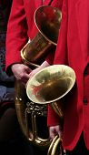 close up of musicians in red suit with theirs saxhorns