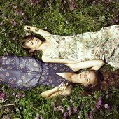 foto of nymph  - Two romantic girl lying on flower meadow - JPG