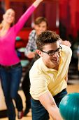 Group of friends in a bowling alley having fun, some of them cheering the one in charge to throw the