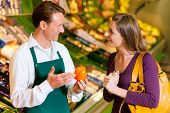 woman in a supermarket at the vegetable shelf shopping for groceries, a shop assistant is helping he