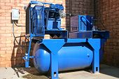foto of air compressor  - bright blue air compressor on commercial building - JPG