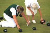 stock photo of crown green bowls  - Two senior women enjoying a game of bowls measuring the distance from the jack - JPG