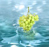 bunch grape falling in a refreshing drink