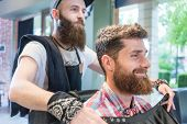 Side view of a handsome young bearded man smiling before having a trendy haircut done by his trustwo poster