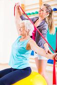 Senior woman with stretch band in fitness gym being coached by personal trainer poster