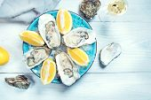 Fresh Oysters close-up on blue plate, served table with oysters, lemon and ice. Table top view. Heal poster