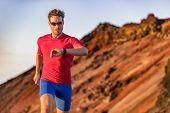 Athlete runner checking cardio on sports smartwatch jogging on outdoor run track. Running man wearin poster