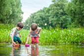 Two Little Brothers Playing With Paper Boats By A River On Warm And Sunny Summer Day. poster