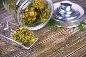 Detail of cannabis buds (scout master strain) on glass jar over wood background - medical marijuana  poster