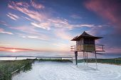 stock photo of shacks  - lifeguard hut on australian beach at sunrise with interesting clouds in background  - JPG