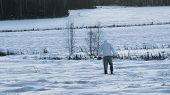 A Person On A Snowy Field. Rear View On Man Walking On Deep Snowy Field. Man Walking In Snow Back Vi poster