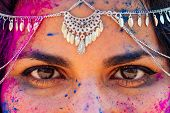Young Indian Face In Paint Woman In Traditional Indian Pink Outfit With Jeweler Celebrating Holi Col poster