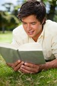 Man smiles while he reads a book as he lies prone on the grass