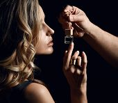 Portrait Of Young Sexy Blonde Woman Smelling Perfume That Man Holds In Front Of Her Face, Touching A poster