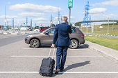Man In A Blue Suit With A Suitcase Walking To His Car And Calling By Phone At The Airport Parking. B poster