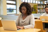 Focused Student Working In Library Computer Class. Young Black Woman Sitting At Desk And Using Lapto poster