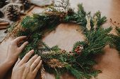 Hands Holding Christmas Wreath With Fir Branches, Berries, Pine Cones, And Thread, Scissors On Rural poster