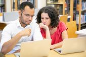 Adult Female Student Consulting Monitor Of College Mate In Library. Man And Woman In Casual Sitting  poster