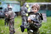 Boy in the camouflage holds a paintball gun barrel up in one hand and protective helmet in another,