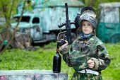 image of bus-shelter  - Boy in the camouflage suit holds a paintball gun barrel up - JPG