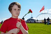 Boy in the red t-shirt with red pink in the hands stands on Poklonnaya Hill on Victory Day.