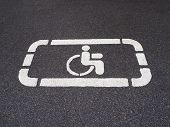 White Handicapped Symbol Of Wheelchair Painted On Asphalt On A Parking Lot, Sign Of Parking Space Fo poster