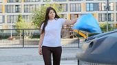 Young Woman Throws A Bag Of Garbage Into The Tank Near The House. poster