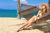 Elegant woman in a bikini reclining in a hammock strung between palm trees on the beach at a tropical resort