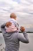 Baby In The Arms Of Dad. Walk Near The Water. Baby And Dad Against The Sky. poster